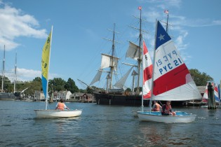 Conrad campers learning to sail on the Mystic River alongside the tall ship Joseph Conrad.