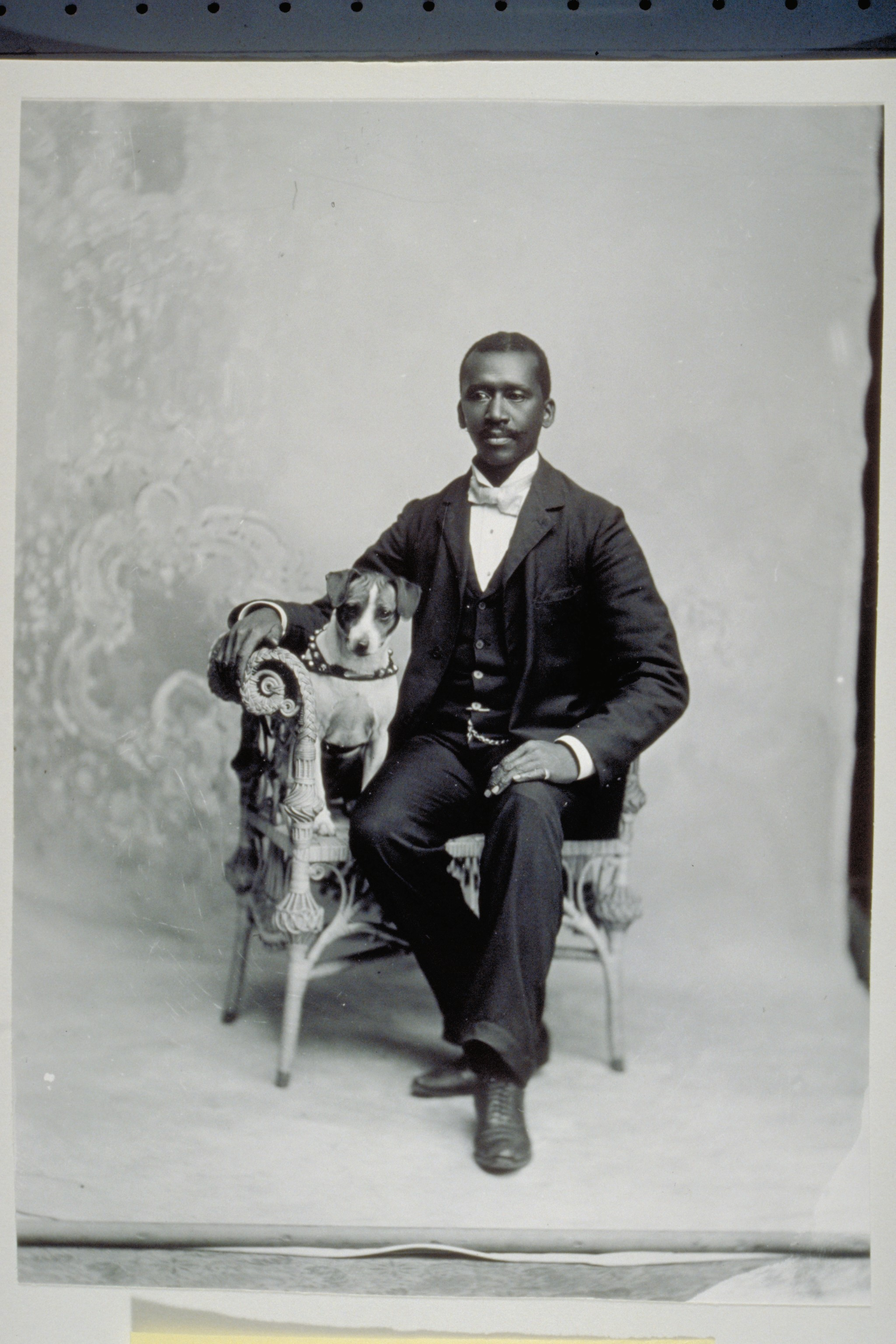 "Studio portrait of a black man identified as Edward Wiggins. A dog sits beside him in a wicker chair. ""Edw. [Edward] Wiggins"" is scratched on the plate. Circa 1890-1899. Photo Credit: Mystic Seaport Museum MSM 1977.160.1171"