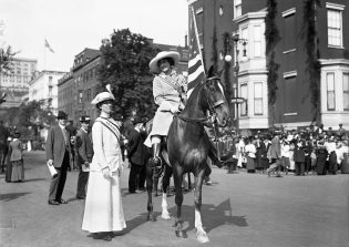 Misses Beiderhase and Milholland, 1912. Shot in New York City, May 4, 1912. Image of two women suffragists wearing banners. The woman on the left standing, is Josephine Beiderhase. The woman on the right seated on a horse carrying an American flag is Inez Milholland. (Mystic Seaport Rosenfeld Collection ANN.1984.187.6818)