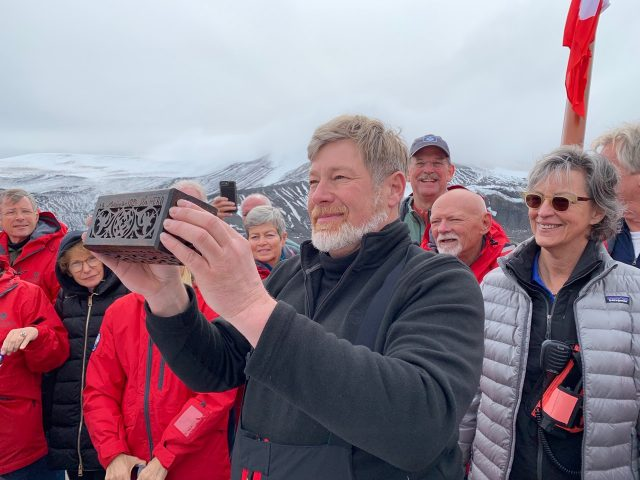 Museum trustee Alex Bulazel holds up the ditty box that traveled with Palmer to Antarctica at Seception island on January 27, 2020. Credit: Amanda Bulazel