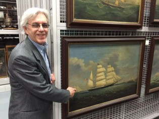 Image: Mystc Seaport Paul O'Pecko with a painting in the collections storage vault.