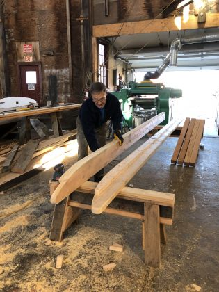 Volunteer Bill Salancy sands the replica sledge's two 16-foot long runners in the Henry B. duPont Preservation Shipyard. Photo by Elissa Bass/Mystic Seaport Museum